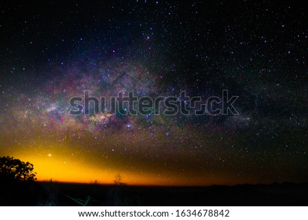 Night landscape with colorful Milky Way and yellow light at mountains. Starry sky with hills at summer and sunshine day. Beautiful Universe. Space background. (noise pic)