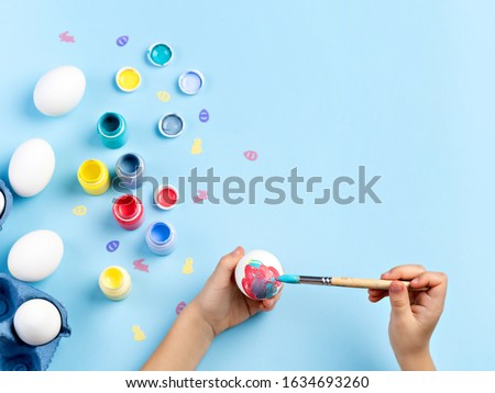 Easter eggs decorating activity. Close up image of kids hands painting an egg. Bottles of various paint, white eggs, bunny and chicken shaped sequins, brushes are around. Top view, space for text.
