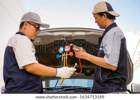 Two mechanical engineer wear uniform fix a car with manifold gauge and car background #1634713189