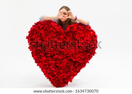 a girl with a huge red heart on a white background looks through fingers folded into a heart shape. Banner for the day of all lovers