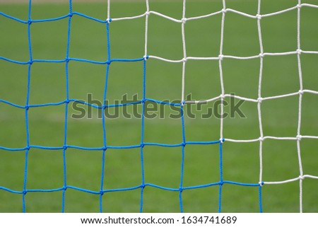 Soccer or football net background, back view of goal with blurred stadium and field field field. #1634741689