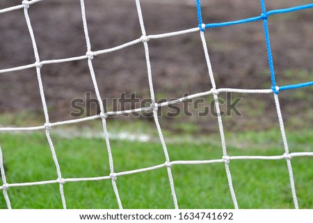 Soccer or football net background, back view of goal with blurred stadium and field field field. #1634741692