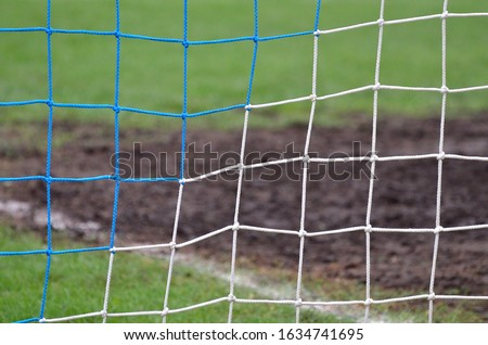 Soccer or football net background, back view of goal with blurred stadium and field field field. #1634741695