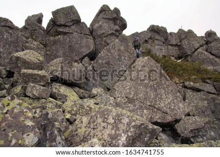 Southern Urals. A mature tourist makes an ascent to the top along a large stone placer. #1634741755