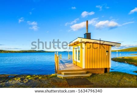 Lake yellow cabin scene view. Sauna at lake shore. Yellow sauna cabin on lake shore. Lake house view #1634796340