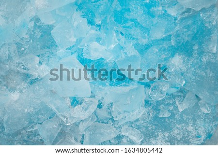 Pieces of crushed blue ice glass cracks background texture. close-up frozen water