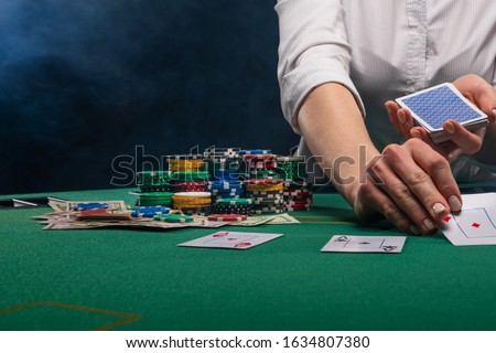 The croupier deals cards in a casino, for playing poker, against the background of the table, chips. Gaming business in Las Vegas