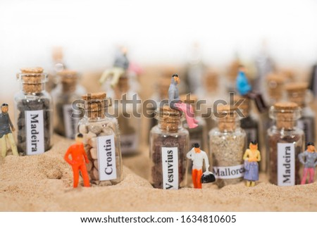 Glass test-tube with sand of different summer vacation destinations. Located in sand with small people figures. #1634810605