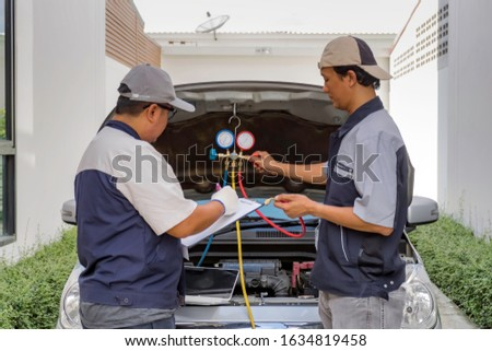 Two mechanical engineer wear uniform fix a car with manifold gauge and car background. selective focus #1634819458