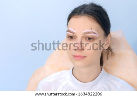 Portrait of woman with painted shape of eyebrows on face before tinting in beauty clinic. Girl is sitting and waiting cosmetologist. Preparing to painting eyebrow procedure, shaping brows. #1634822206