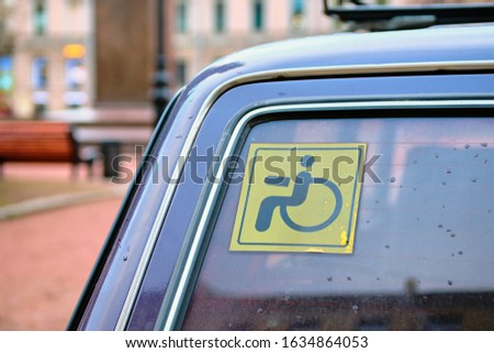 Sign of a man in an armchair - disabled person on the rear window of a car. close up.