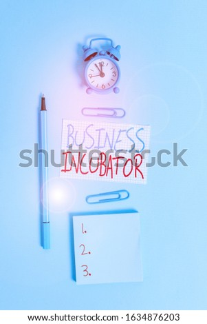 Conceptual hand writing showing Business Incubator. Business photo text company that helps new and startup companies to develop Alarm clock squared paper notepad marker clips colored background. #1634876203