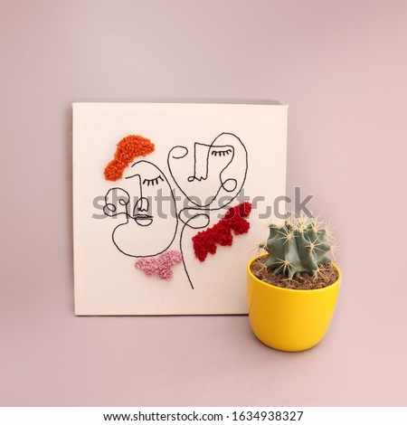 Embroidery fabric punch frame, fabric poster with one line cute girl drawings with a cactus in yellow pot, minimal handicraft image Royalty-Free Stock Photo #1634938327