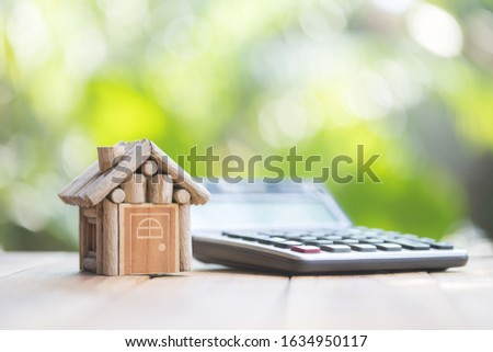 The house is placed beside the calculator, natural blurred green background. planning savings money of coins to buy a home concept for property, mortgage and real estate investment.to buy a house. #1634950117