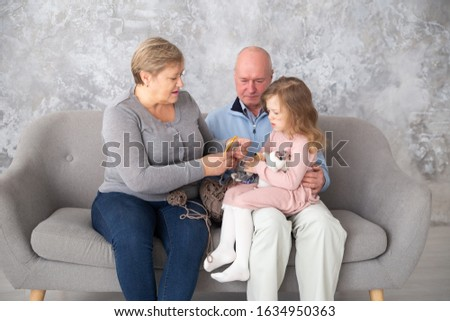 Grandmother and grandfather knitting together with her granddaughter at family home. Woman with little girl crochet sitting on a sofa in the living room. #1634950363