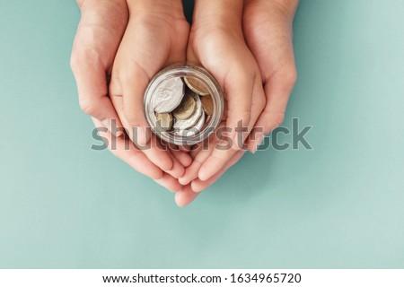 child and parent hands holding money jar, donation, saving, charity, family finance plan concept, Coronavirus economic stimulus rescue package, superannuation concept #1634965720