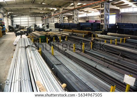 Lots of construction materials in the warehouse interior. Different construction objects for sale in factory work place: Heavy chrome proiles, pipe, tubes for reinforcement or new construction #1634967505
