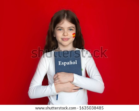little girl advertises spanish language school, learning spanish concept, portrait on red background. Spanish is written on a notepad (in Spanish) #1635038485