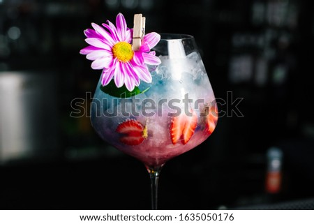 Strawberry and flower decorated drink in wine glass #1635050176