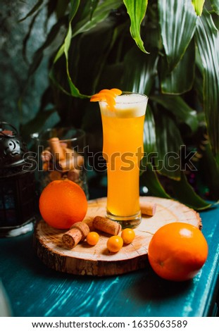 Orange decorated cocktail with wooden background #1635063589