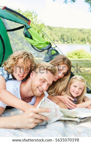 Parents and two children in tent together planning a trip in summer vacation #1635070198
