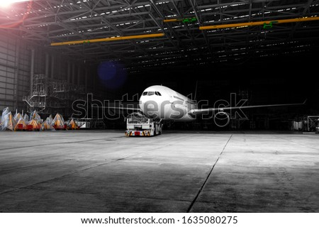 Aircraft towing tractors towing aircraft (airplane) out from aircraft hangar after finished maintenance. Royalty-Free Stock Photo #1635080275
