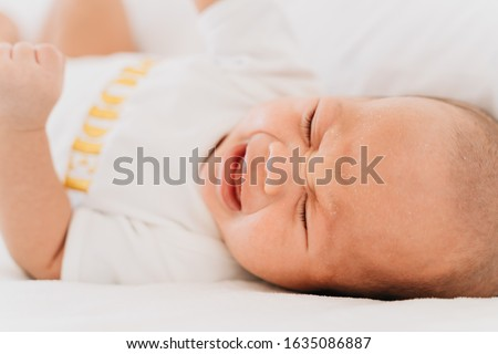 Close up shot of crying newborn baby on bed at home. Hungry baby infant boy cry for milk #1635086887