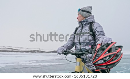 Woman stands near her bike on ice. The girl cyclist stopped to rest. The beautiful view of the sunset. The traveler is ride a cycle. Female is riding bike on the ice. Athlete puts on gear. #1635131728