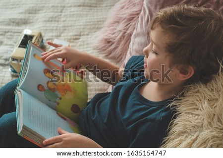 Child reading book. Kids read books. A little boy sits on a bed with your toys in living room watching pictures in story book