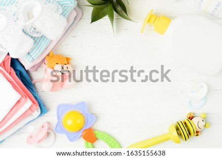 Colorful baby asccessories and clothes flat lay on white wooden background. Baby shower concept with pacifier, toys, bodysuits and ratller #1635155638