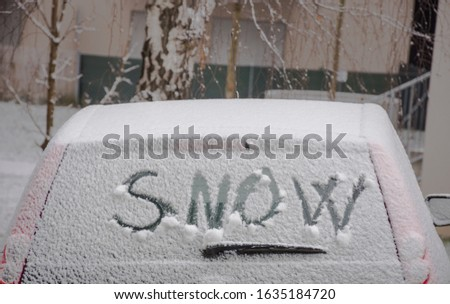 The word SNOW written in fresh snow on the windscreen of a car #1635184720