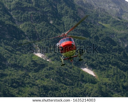 helicopter carries cargo in the Alps at a construction site #1635214003