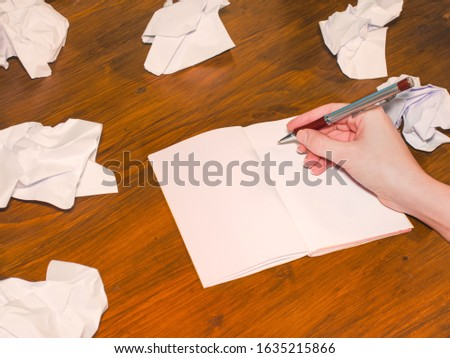 A hand writes in a blank empty notebook with crumpled sheets of paper around. Wooden table background. Selective focus. Creativity or writing concept. #1635215866