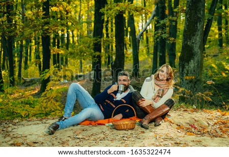 Romantic couple in love have a date at beautiful autumnal park. Man and woman wearing warm cozy clothes and drinking a cup of hot tea. Young family couple. Family concept