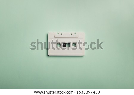 White vintage cassette on pastel plain background, indie, mixtape, old.