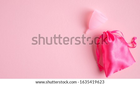 Menstrual cup with case on pink background. Top view with copy space. Alternative feminine hygiene product. Women health care concept. #1635419623