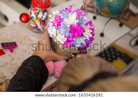 A young blond woman is writing a note on a floral arrangement. The arrangement is made of white, purple and pink chrysanthemums placed in a wooden bark box. #1635426181