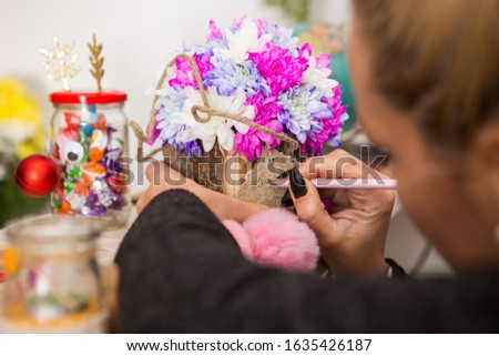 A young blond woman is writing a note on a floral arrangement. The arrangement is made of white, purple and pink chrysanthemums placed in a wooden bark box. #1635426187
