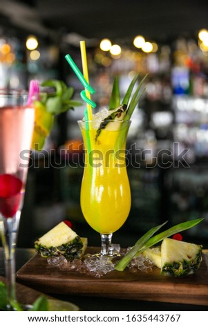 Pineapple and red cocktail with wooden background #1635443767