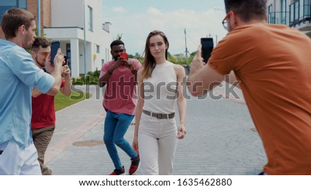 Attractive fashion model walking in the street among annjoying paparazzi taking silly pictures using smartphones swinging around and having fun.