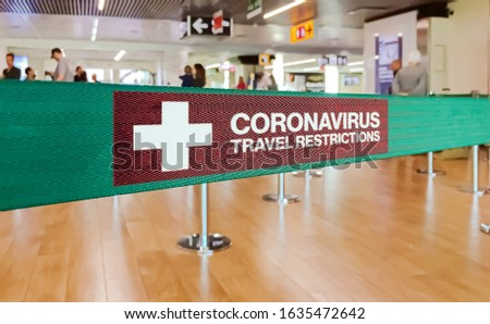 Green ribbon barrier inside an airport with the warning of travel restrictions due to the spread of the dangerous Coronavirus #1635472642