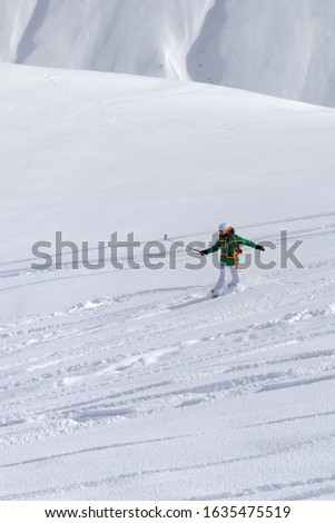 Snowboarder downhill on snowy off piste slope with newly-fallen snow at high winter mountains. Caucasus Mountains. Georgia, region Gudauri. #1635475519