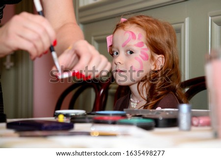 Beautiful girl make up as a butterfly. Make-up for children's party.Child animator, artist's hand draws face painting to little girl.