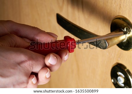 Photo of female hands, with screwdriver, tightening door hinge Royalty-Free Stock Photo #1635500899