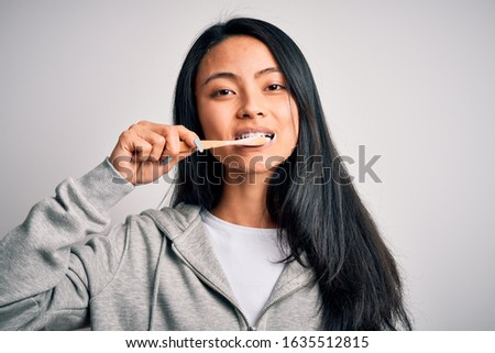 Young beautiful woman smiling happy. Standing with smile on face whasing tooth using toothbrush over isolated white background #1635512815