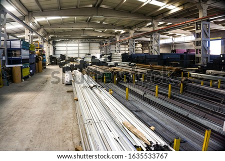 Lots of construction materials in the warehouse interior. Different construction objects for sale in factory work place: Heavy chrome proiles, pipe, tubes for reinforcement or new construction #1635533767