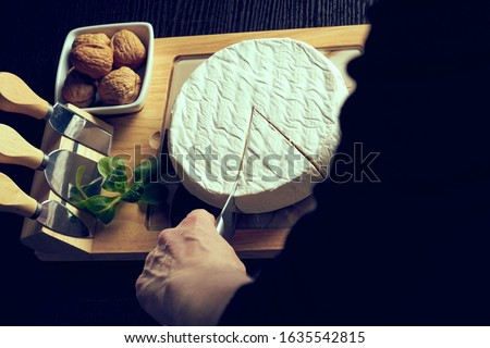 Closeup on woman cutting fresh cheese at desk. Royalty-Free Stock Photo #1635542815
