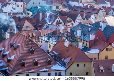 Snow covered rooftops from tiles, Smoke comming from chimneys on cold day. Pollution concept. Aerial cityscape view of Cesky Krumlov Old Town on winter day. #1635557995