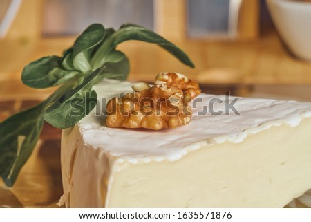 Cheese peaces on the old wooden table in the kitchen. Dairy product. Healthy eating and lifestyle. Royalty-Free Stock Photo #1635571876