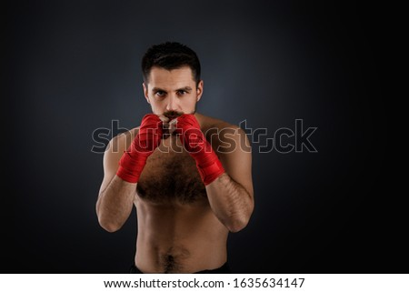 boxer man with bandage on hands training before fight and showing the different movements on black background #1635634147